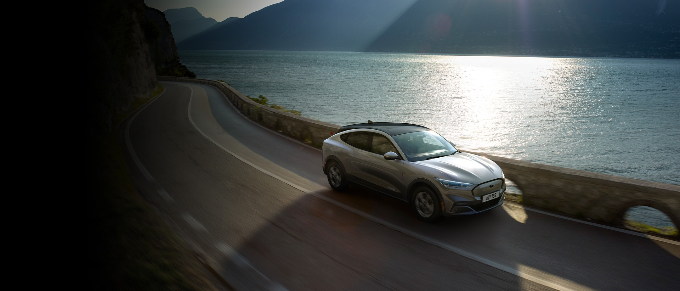 All-New Ford Mustang Mach-E in motion driving past the lake